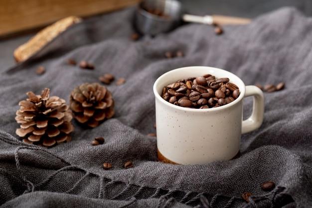 Grãos de café em uma xícara branca em um lenço cinza Foto gratuita