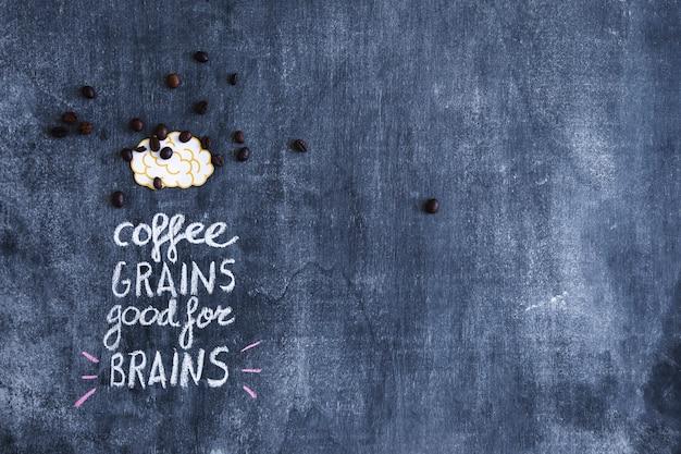 Grãos de café espalhados no cérebro de recorte de papel com texto na lousa Foto gratuita