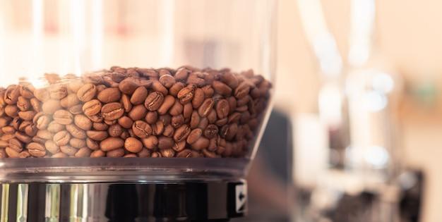 Grãos de café na máquina de torrador para fazer pó para café da manhã no café Foto Premium