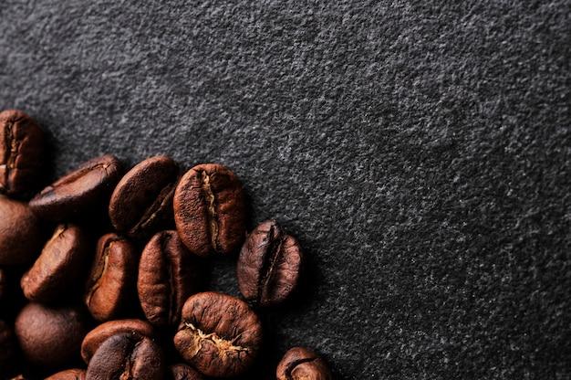 Grãos de café no fundo de pedra escura Foto Premium