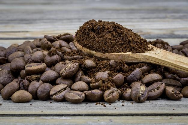Grãos de café perfumados em uma linda colher de pau na madeira Foto gratuita