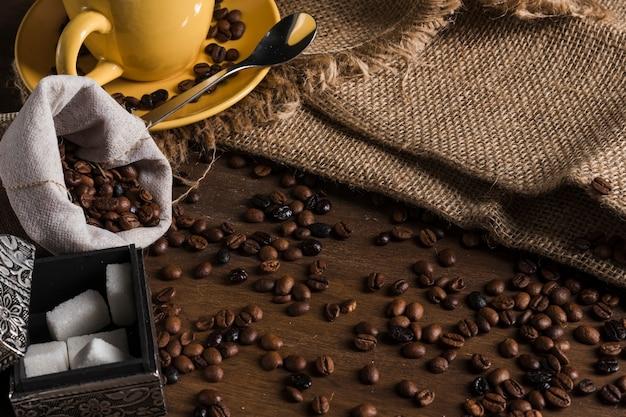 Grãos de café perto de saco, jogo de chá, caixa de açúcar e pano de saco Foto gratuita
