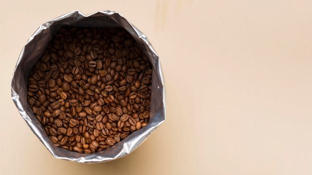 Grãos de café pretos sobre fundo bege com espaço de cópia Foto gratuita