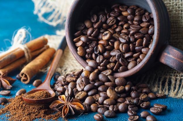 Grãos de café saindo de um copo de barro e espalhados em uma textura azul Foto Premium