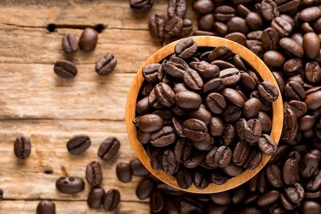 Grãos de café sobre fundo de madeira Foto Premium