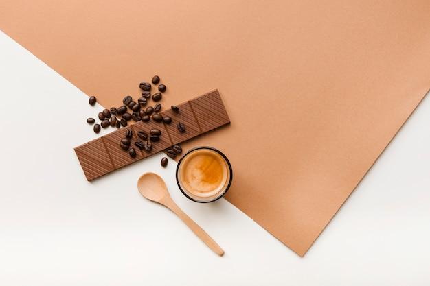 Grãos de café torrados; barra de chocolate e copo de café com colher no fundo Foto gratuita