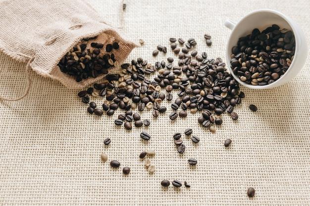Grãos de café torrados caindo do saco e copo cerâmico Foto gratuita