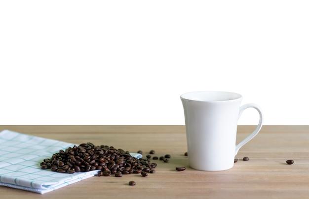Grãos de café torrados com xícara de café em madeira. fundo isolado. Foto Premium
