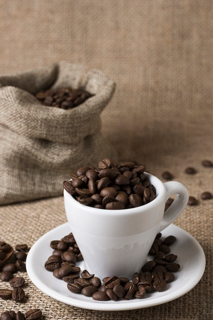 Grãos de café torrados em copo branco Foto gratuita
