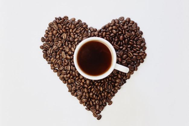 Grãos de café torrados em forma de coração e café em branco Foto Premium