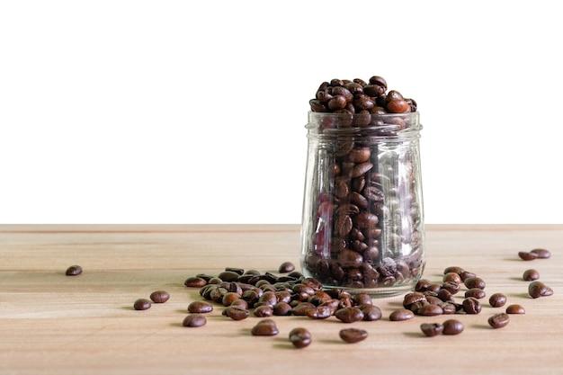 Grãos de café torrados em garrafas de vidro colocadas sobre o fundo da mesa isolado. Foto Premium