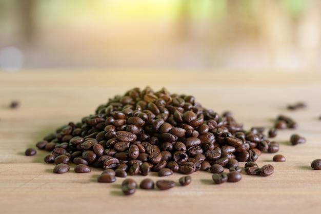 Grãos de café torrados em madeira com fundo de natureza. Foto Premium
