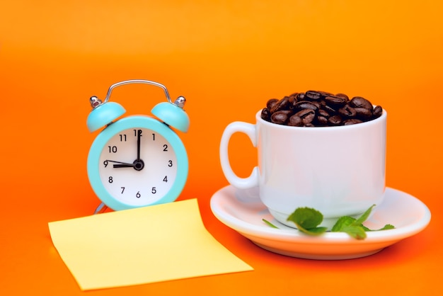 Grãos de café torrados em uma xícara de café branco tem folhas verdes e um despertador e em um fundo laranja e um adesivo para registrar Foto Premium