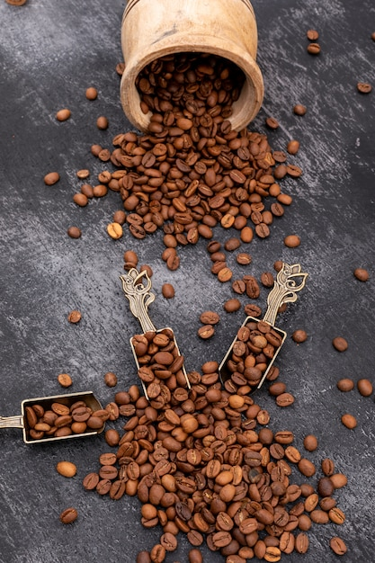 Grãos de café torrados na colher de metal na superfície preta Foto gratuita