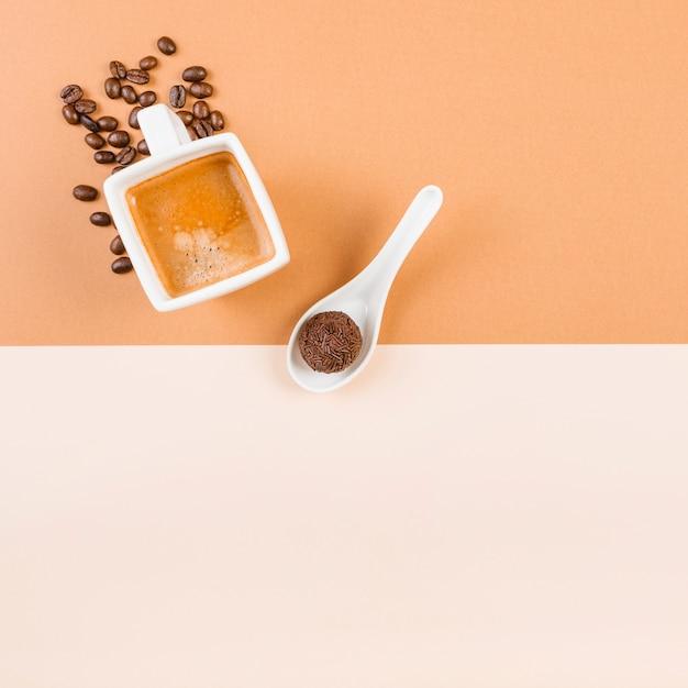 Grãos de café torrados; xícara de café e bola de chocolate na colher em pano de fundo duplo bege Foto gratuita