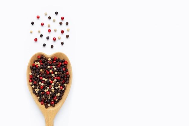 Grãos de pimenta pretos, vermelhos e brancos com colher de pau branco Foto Premium