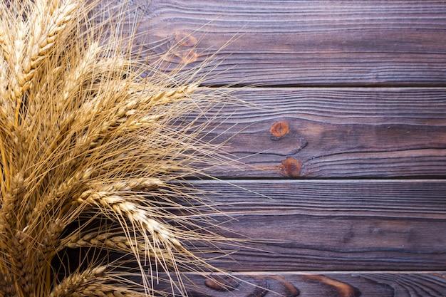 Grãos de trigo no fundo de prancha de madeira conceito de colheita Foto Premium