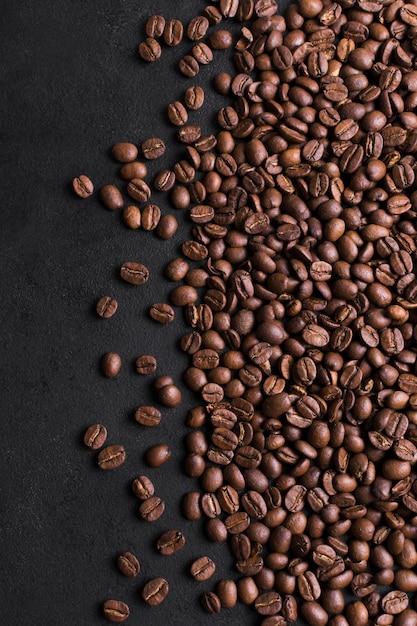 Grãos torrados de café de bom gosto em fundo preto Foto Premium