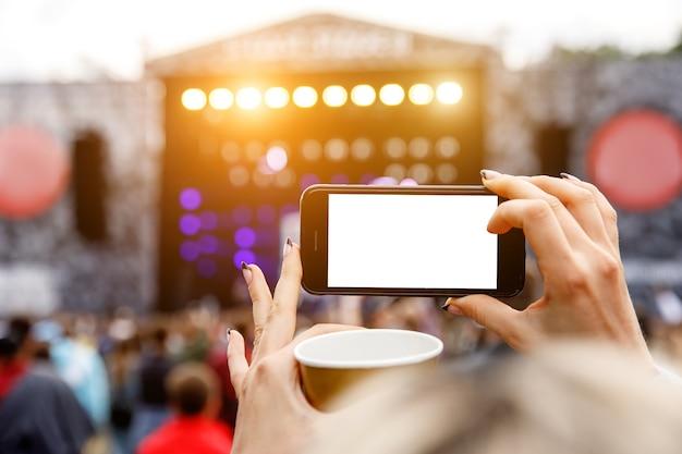 Gravação de concerto de música ao ar livre em um telefone celular. tela em branco Foto Premium