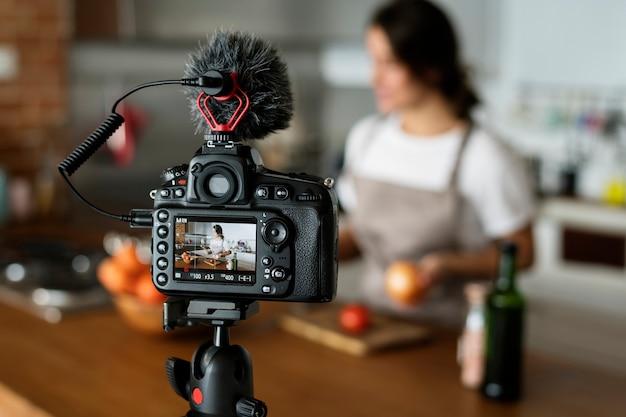 Gravação de vlogger feminino cozinhar transmissão relacionada em casa Foto gratuita