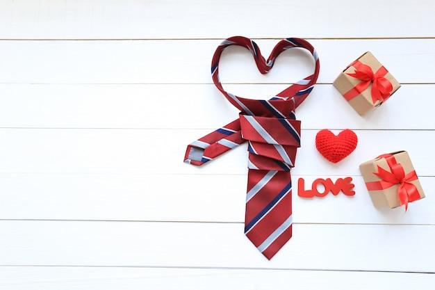 Gravata de coração vermelho e caixa de presente com fita vermelha e coração artesanal de crochê em fundo de madeira para o dia dos pais feliz Foto Premium