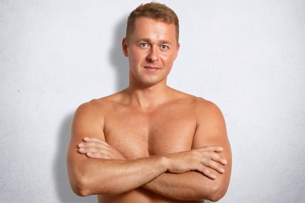 Grave auto-confiante masculino com corpo musculoso, mantém as mãos cruzadas, fica nua contra a parede de concreto branco Foto gratuita