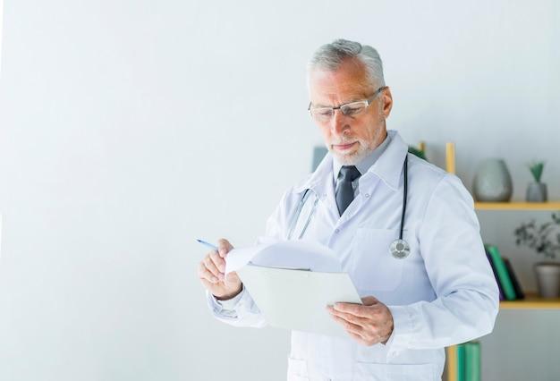 Grave doutor lendo registros Foto gratuita