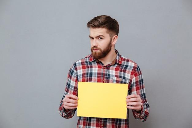 Grave homem barbudo segurando papel em branco Foto gratuita