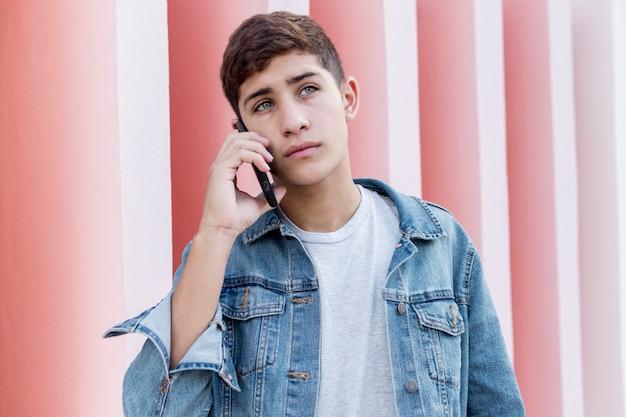 Grave jovem adolescente falando no celular no exterior Foto gratuita