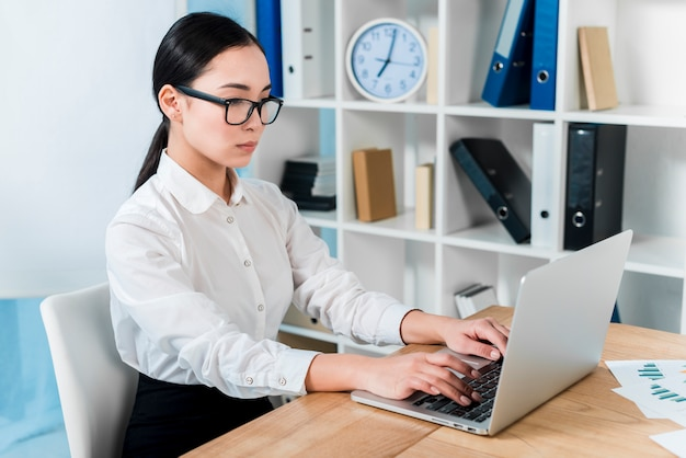 Grave jovem empresária digitando no laptop sobre a mesa Foto gratuita
