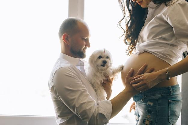Gravidez e pessoas conceito - homem feliz abraçando sua esposa grávida em pé na janela em casa Foto Premium
