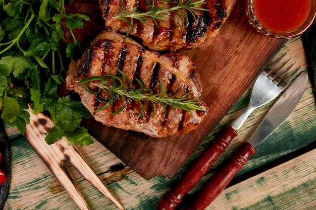 Grelha de carne de porco bife na tábua de madeira Foto Premium