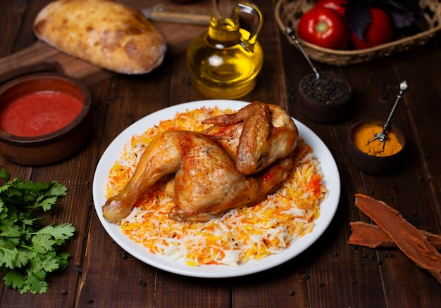 Grelha de frango inteiro servido com guarnição de arroz em chapa branca Foto gratuita