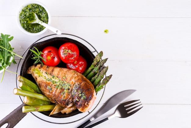 Grelha de peito de frango com legumes para churrasco e molho pesto em uma panela de ferro fundido em branco Foto Premium