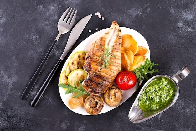 Grelha de peito de frango com legumes para churrasco e molho pesto em uma panela de ferro fundido Foto Premium