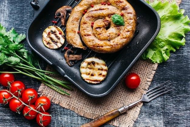 Grelhe a panela com salsicha grelhada deliciosa espiral e vegetais Foto gratuita