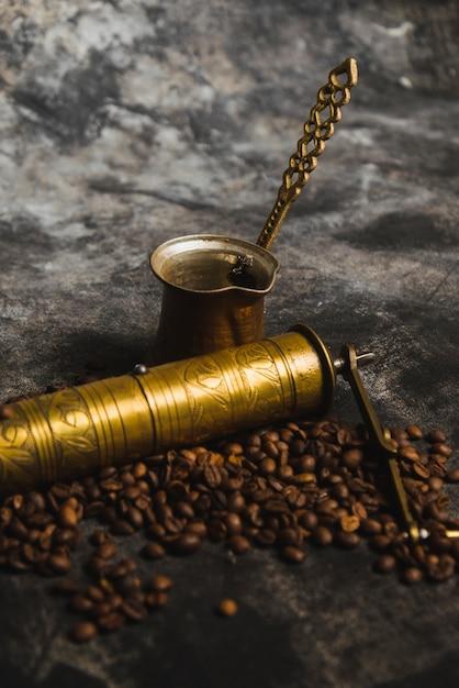 Grinder e cezve perto de grãos de café Foto gratuita