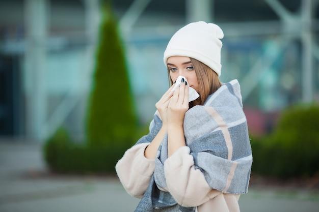 Gripes e resfriados. mulher jovem e atraente ao ar livre com tecido branco Foto Premium