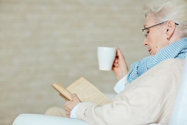 Grisalho mulher sênior com livro emocionante Foto gratuita