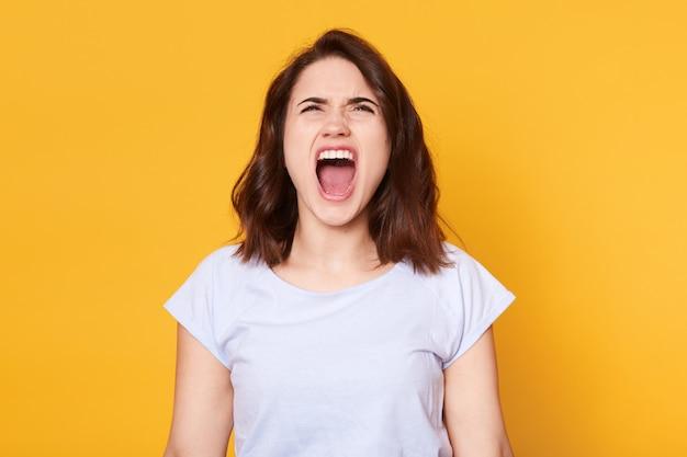 Gritando emocional mulher irritada coloca isolado sobre o estúdio amarelo Foto gratuita