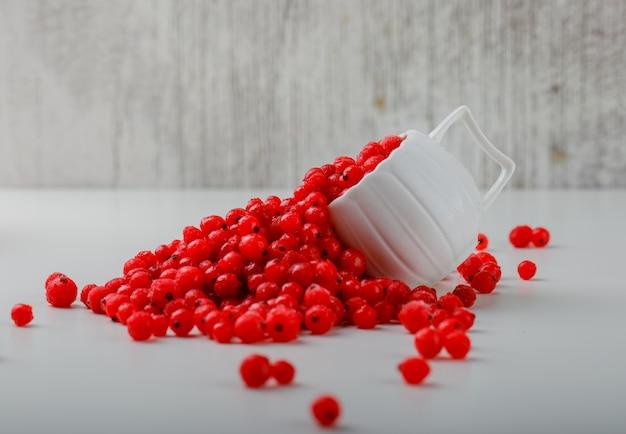 Groselhas dispersas em um copo branco. Foto gratuita