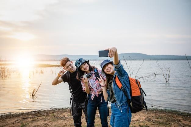 Grupo asiático de jovens com amigos e mochilas caminhando juntos e amigos felizes estão tirando foto e selfie, relaxe o tempo nas viagens de férias Foto Premium