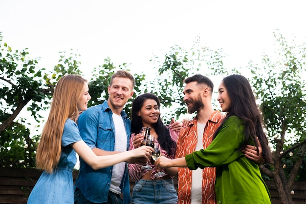 Grupo baixo ângulo de amigos junto com bebidas Foto gratuita