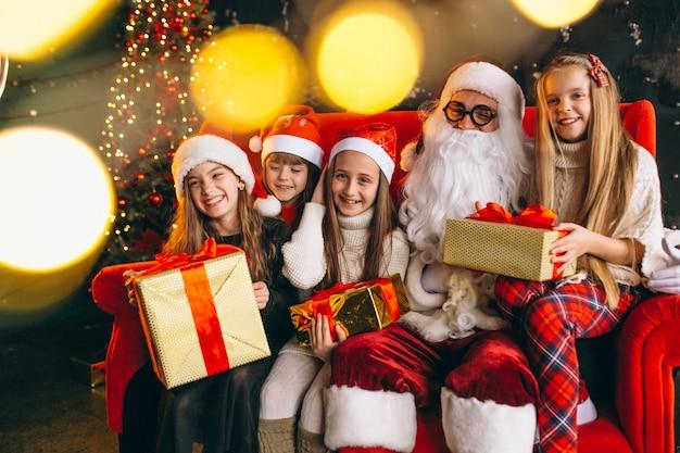 Grupo crianças, sentando, com, santa, e, presentes, ligado, véspera natal Foto gratuita
