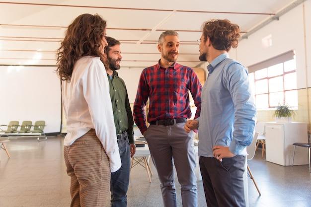 Grupo criativo discutindo idéias, de pé em círculo Foto gratuita
