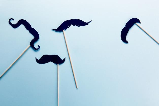 Grupo de acessórios em forma de bigodes pretos em varas em azul cinza com espaço de cópia. Foto Premium