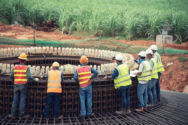 Grupo de aço de instalação de trabalhador de construção re barra em fundação grande Foto Premium