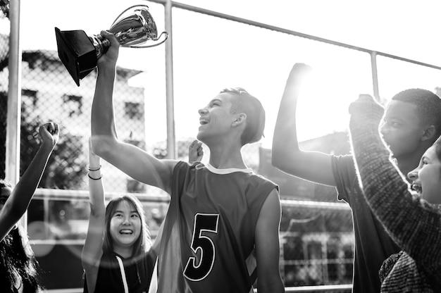 Grupo de adolescentes torcendo com vitória troféu e conceito de trabalho em equipe Foto gratuita