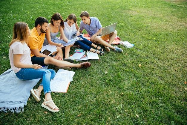Grupo, de, alegre, estudantes, adolescentes, em, casual, equipamentos, com, note livros, e, laptop Foto gratuita