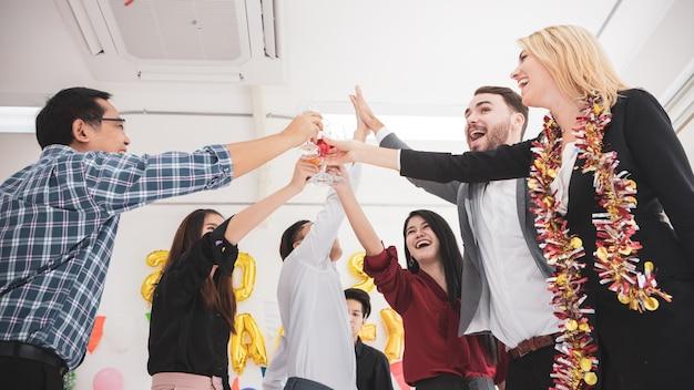 Grupo de amigo que comemora guardar flautas do champanhe ao dançar. Foto Premium